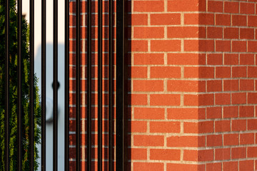 Wrought iron fence attached to red brick post
