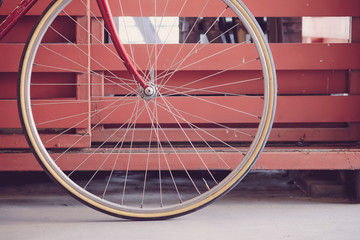 Front wheel of a red bicycle against a fence wall.