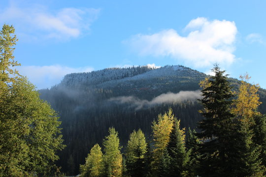 Snoqualmie Pass ,Washington, The first snow of the year its just a dusting . The clouds in the blue sky and the fog along the mountain side. the trees are showing fall colors .