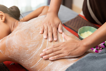 Asian woman enjoying a salt scrub massage at spa.