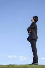 青空をバックに斜め上を向き考え事をするビジネスマンの横姿全身。希望・夢・展望・自由イメージ