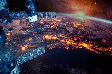 Atlantic coast of the United States night lights and sunrise with lens flare from the space station. Earth with eclipse on starry sky. Elements of this image furnished by NASA.