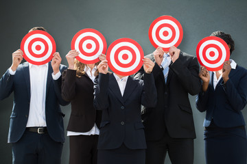 Group Of Businesspeople Hiding Their Faces Behind Dartboard