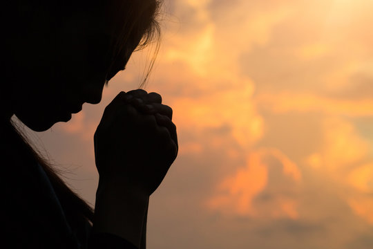 Silhouette of woman hands praying to god with the bible. Woman Pray for god blessing to wishing have a better life. Christian life crisis prayer to god.