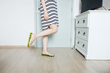 Portrait of Woman in Black and White Stripes Pajamas (Dress). Green Flip-Flops (Sandals). Beautiful Female Standing Isolated at White Room Background