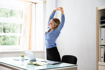 Businesswoman Stretching Her Arms At Workplace