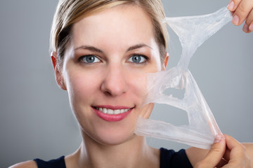 Woman Peeling Off A Facial Mask