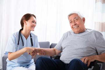 Senior Man Sitting On Wheelchair With Female Nurse