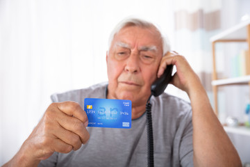 Man With Credit Card Using Landline Phone