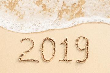 2019 handwritten on sandy beach with soft ocean wave on background