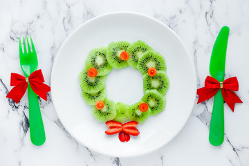 Funny xmas food idea for kids - kiwi strawberry edible Christmas wreath on a white plate