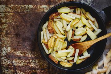 Fried potatoes in a black frying pan top view