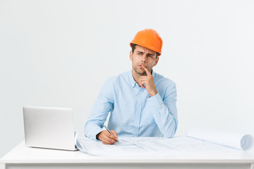 Confident smiling architect in formal wear thinking and working with blueprint papers and drawings in modern lightful office