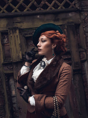 Beautiful woman face in the hat and red hair