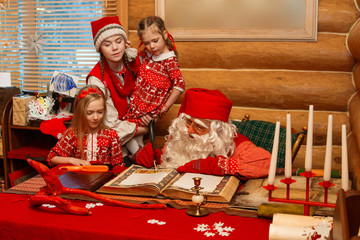 Santa Claus in his office writing a letter to him watching two little girls in beautiful dresses and Christmas elf