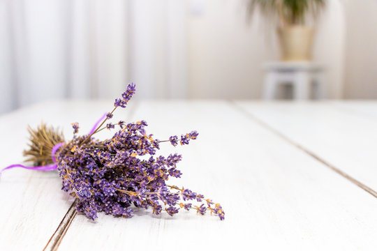 Frontal view of a lavender lying on the table with flower in the background