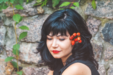 Sexy beautiful pretty brunette with red lipstick with red rose hips