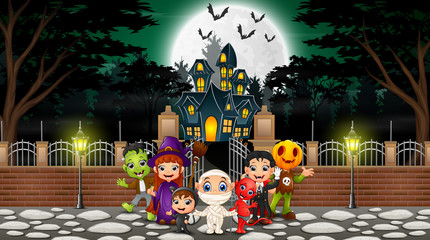 Happy halloween group celebrate in front of haunted house