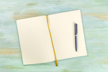A top shot of an open journal with a pen on a teal blue background with a place for text