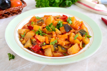 Delicious vegetable stew in a bowl on the table. Stewed potatoes, eggplants, zucchini, onions, carrots in spicy tomato sauce with greens.