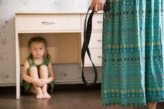 Domestic violence. Mother holding the belt in her hand to punish her small daughter. Scared child hiding under a table and sitting there terrified by physical punishment. Shallow depth of field