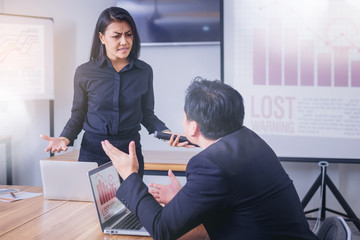 Serious woman boss scolding male employee for bad business result.