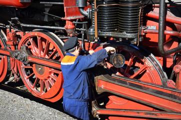 Popovo, Bulgaria, October 6 2018: Mechanic checks steam locomotive iin Popovo, Bulgaria