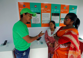 A WhatsApp-Reliance Jio representative explains how to use Facebook Inc's WhatsApp messenger to a woman during a drive by the two companies to educate users, on the outskirts of Kolkata