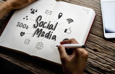 Man drawing social media in a notebook