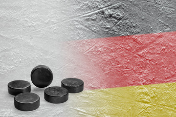 Hockey pucks and the image of the German flag on the ice