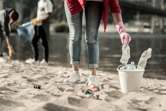 Trash on beach. Active responsible student wearing jeans volunteering while cleaning up trash left behind on the beach