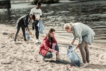 Helpful teacher. Caring blonde-haired teacher wearing denim shirt helping her students volunteering at the beach