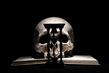 Human skull on old open book with vintage hourglass on black background. Drama and time concept.