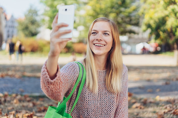 Woman walking down a road in fall taking a selfie