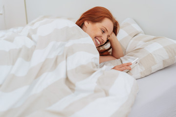 Smiling young woman in bed with smartphone