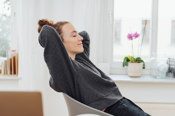 Young woman relaxing leaning back in her chair