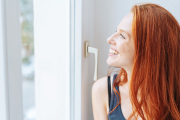 Smiling happy woman looking out of a window