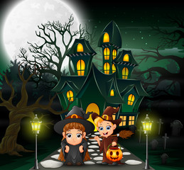 Happy couple witch in front of the haunted house with full moon background