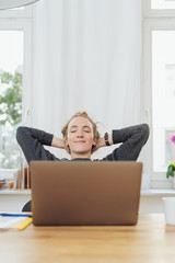 Pleased successful young woman relaxing at work