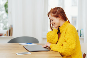 Smiling red haired woman at table with laptop