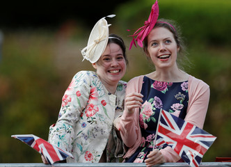 Two women wait near Windsor Castle before the royal wedding of Britain's Princess Eugenie and Jack Brooksbank in Windsor