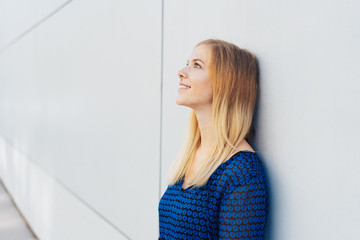 Young smiling woman standing daydreaming