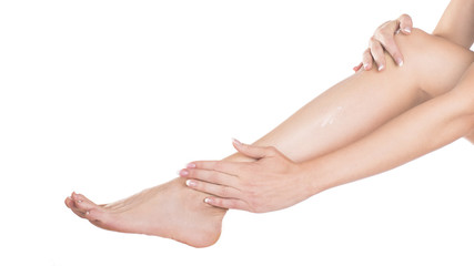 woman apply cream on her bare feet.