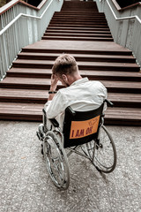 Alone with difficulties. Unhappy depressed disabled man sitting in the wheelchair in front of wooden stairs and having to way of climbing them