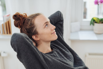 Attractive young woman sitting daydreaming