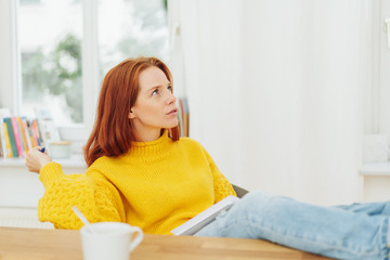 young woman sitting pondering a problem