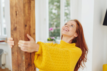 Joyful young woman celebrating at home