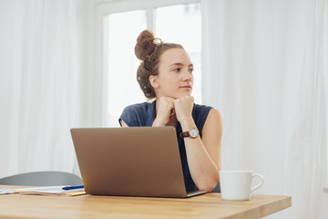 Thoughtful woman sat at table with laptop