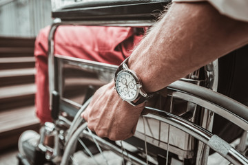 Time. Close up of young person putting hand on the wheel while sitting in the wheelchair