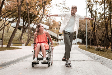 Riding skateboard. Cheerful emotional young man putting hands up and riding a skateboard while spending time with his cute disabled girlfriend